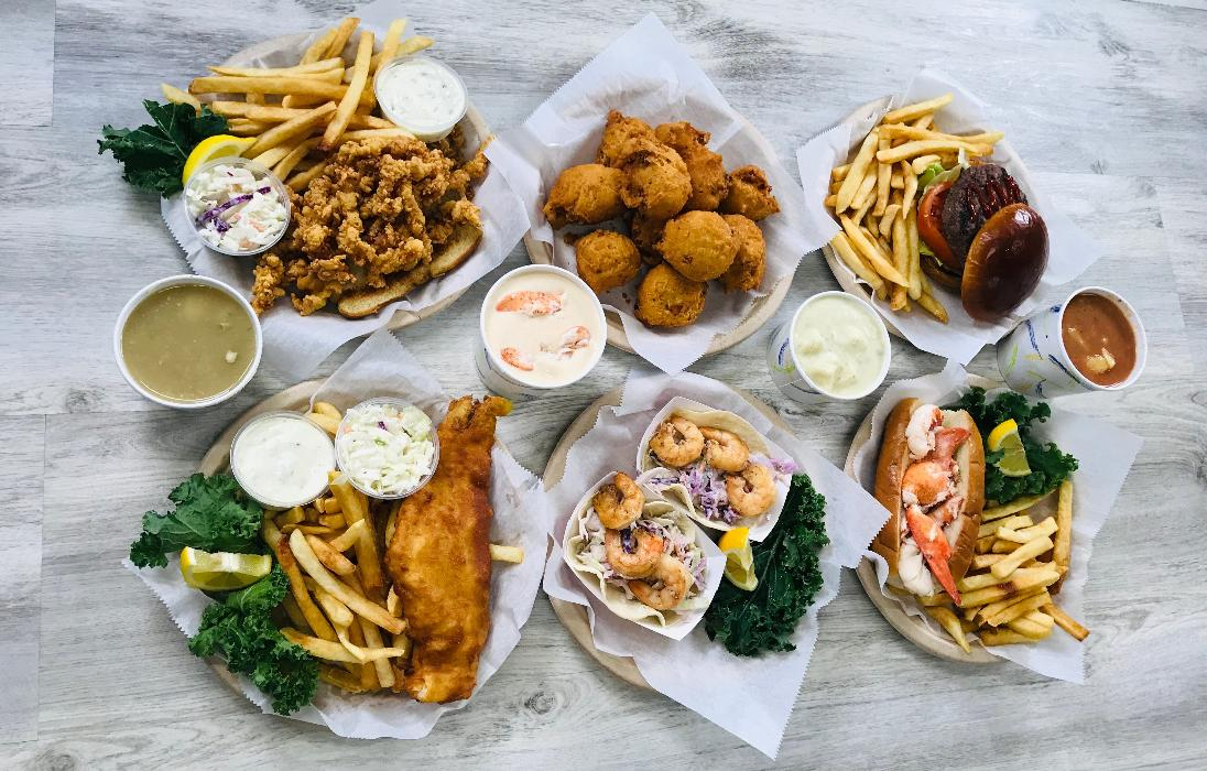 A variety of Chevy's Shack Hot Seafood Menu Options: Chowder, Fish & Chips, Shrimp Tacos, Lobster Roll, Clam Cakes, Burger & Fries and Clam Strip Plate